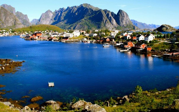 A small boat in a body of water with Lofoten in the background