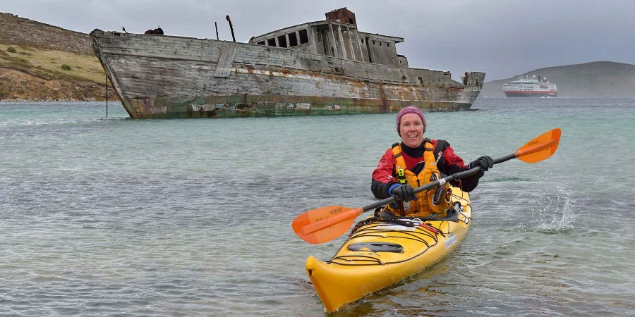 Lady in kayak in front of shipwreck